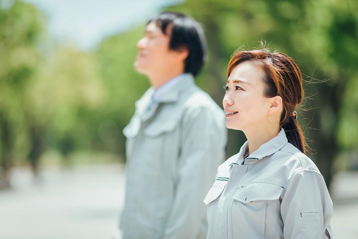 空を見上げる軽作業員2名